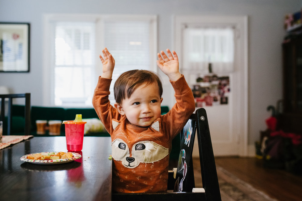 "boy puts his hands up like ""so big"" while at the table eating from family documentary photography session in atlanta"