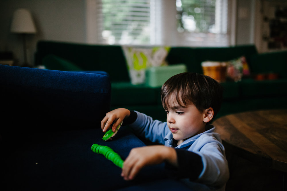 boy plays with toy on the couch during family documentary photography session in atlanta
