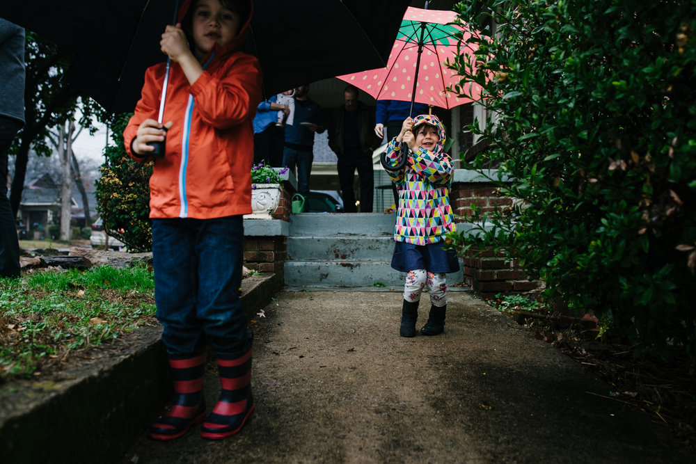 Children with rainboots and umbrellas take a walk in the rain from family documentary photography session in atlanta