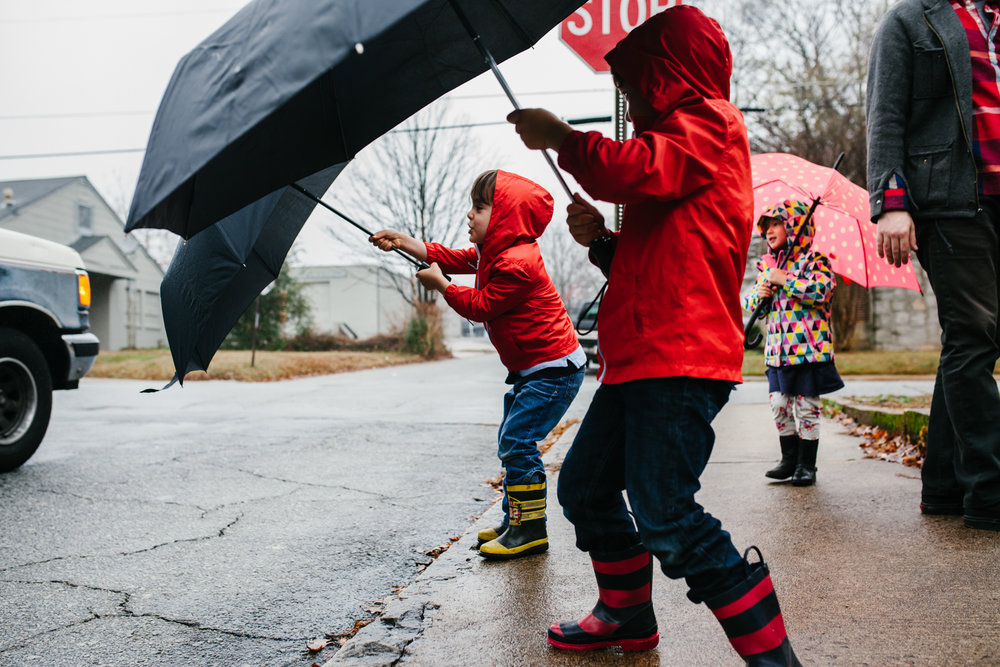 boys in red raincoats put out their umbrellas on the sidewalk during family documentary photography session in atlanta