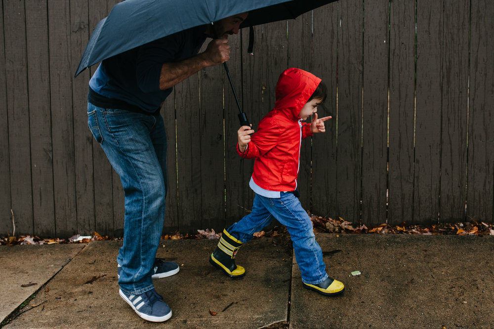 Son leads the way with umbrella as father crouches behind him from family documentary photography session in atlanta