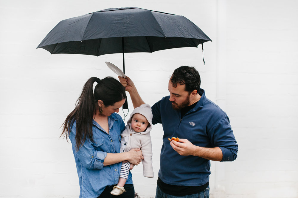 mother holding baby under an umbrella held by dad from family documentary photography session in atlanta