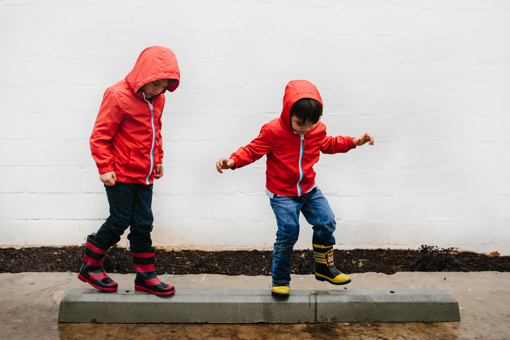 Brothers in rainboots and rainjackets balance in the rain from family documentary photography session in atlanta