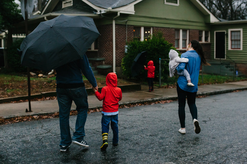 Family walks back home in the rain from family documentary photography session in atlanta