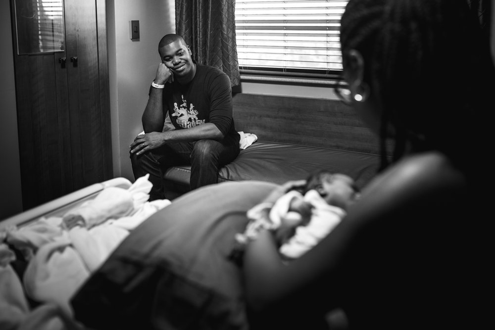 Father looking at newborn and mama from newborn documentary photography session in atlanta
