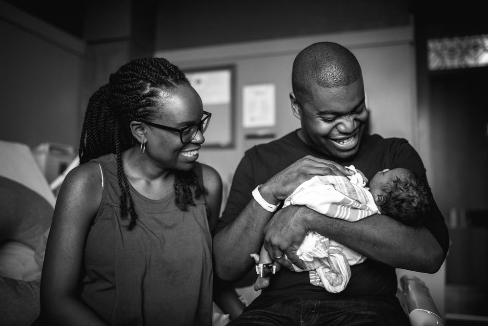 Father smiling while looking at his newborn baby girl from newborn documentary photography session in atlanta