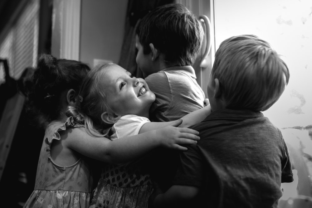 siblings hugging with child looking up and smiling