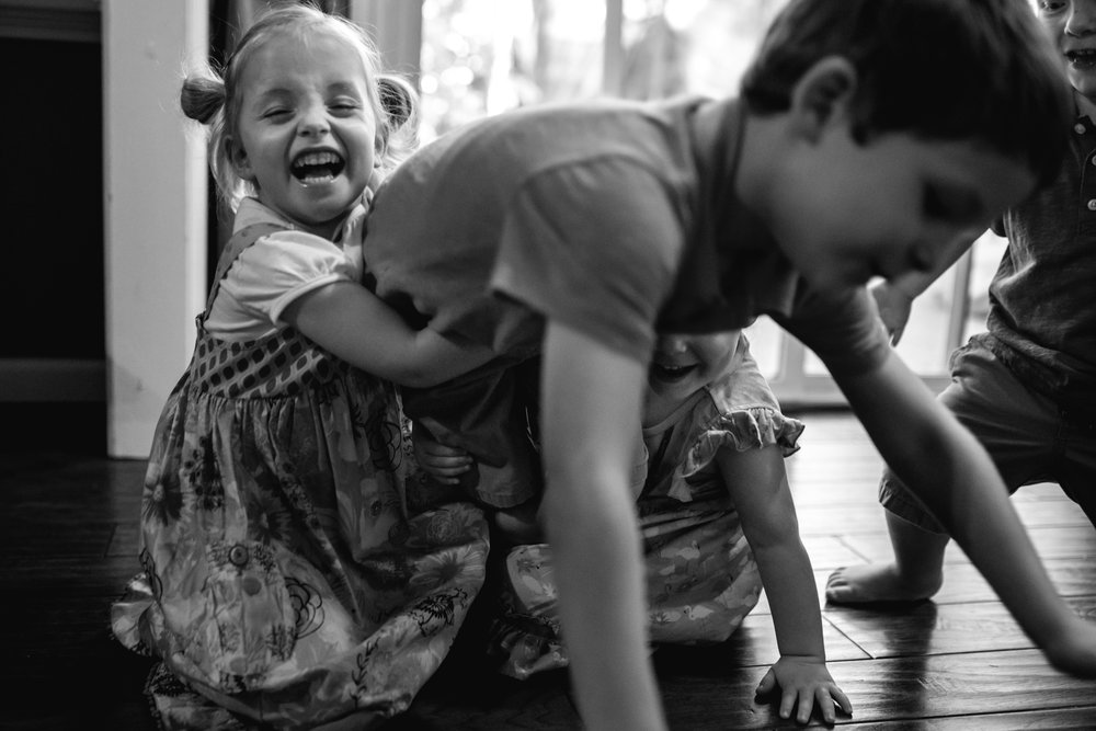 girl smiling and holding brother who is crawling