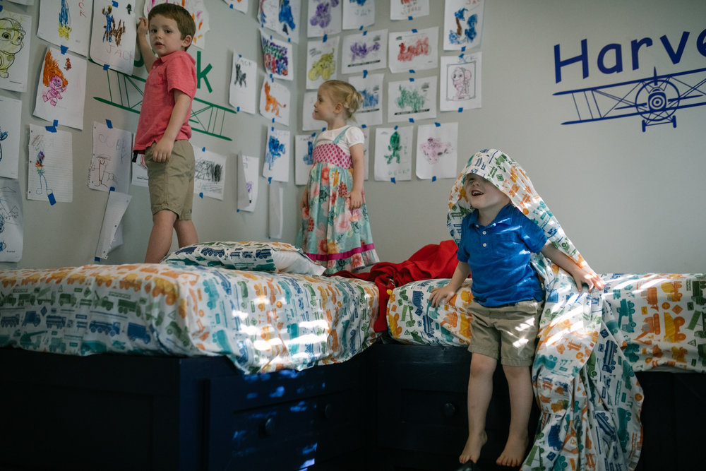 children in bedroom standing on bed looking at art on the walls