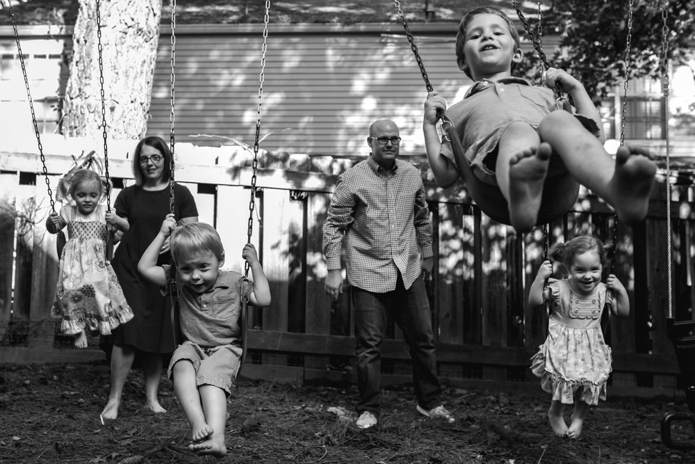 Mom and Dad pushing four children on swings