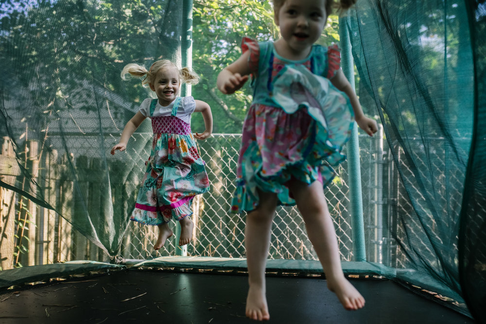 Two girls jumping on a trampoline