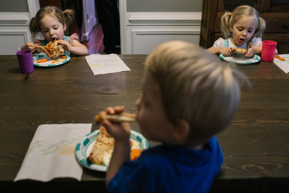 Triplets eating pizza