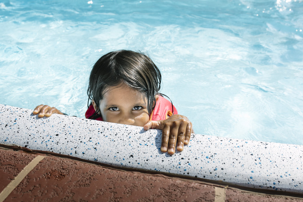 Young girl in the pool peering over the edge