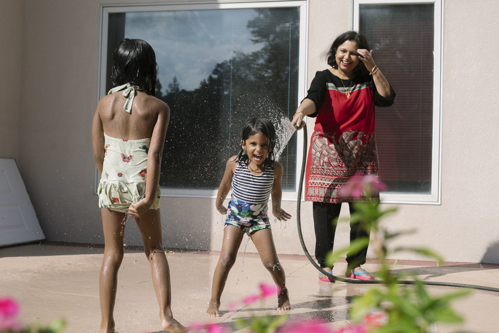 Grandmother spraying her granddaughter with a hose while another girl walks towards them