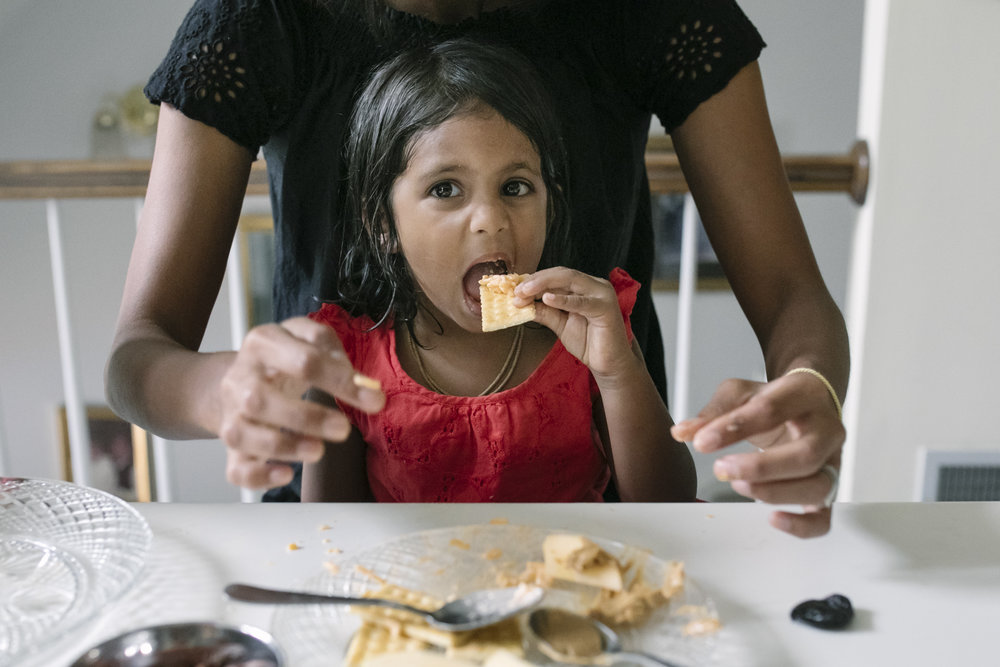 young girl eating a cracker with cheese on it with mother's arms behind her