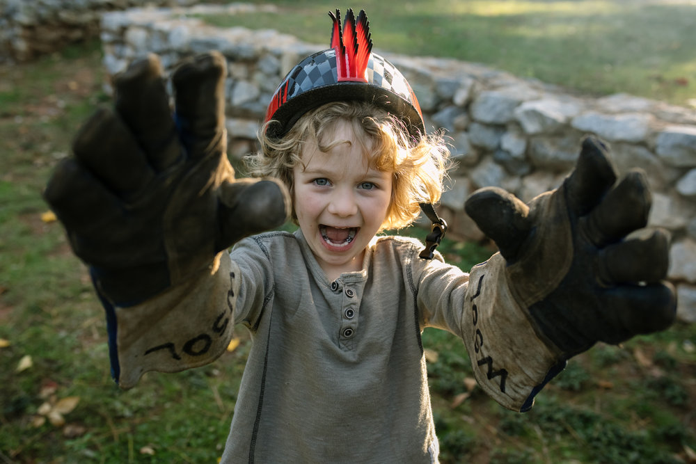 A kid wearing a helmet and oversized welding gloves laughs and looks at the camera