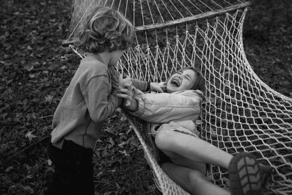 A girl laughs in a hammock as her brother pushes her