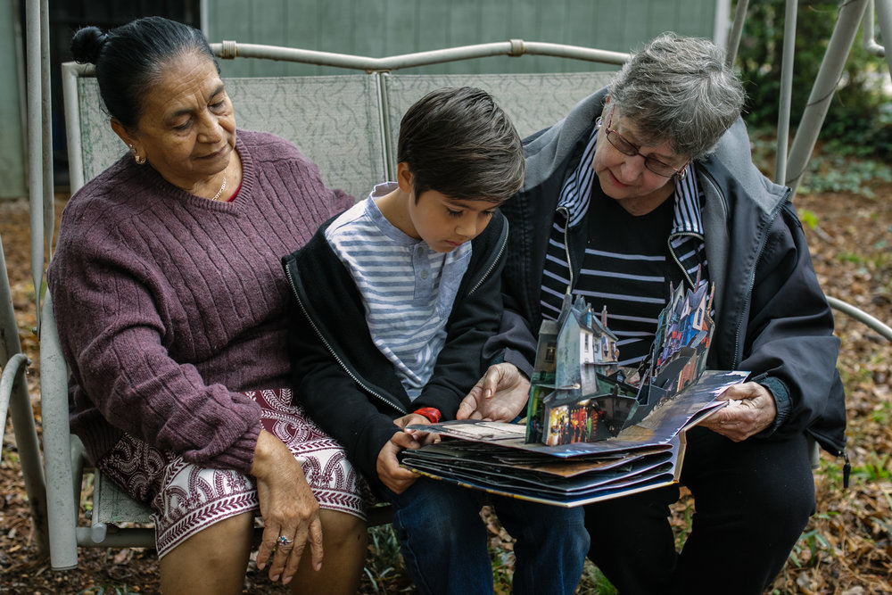 Two grandmothers reading a pop up book to a boy
