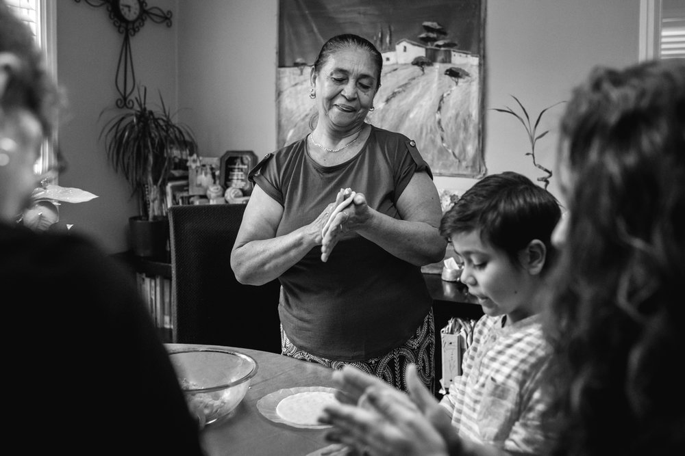 older woman presses a tortilla she's making between her hands