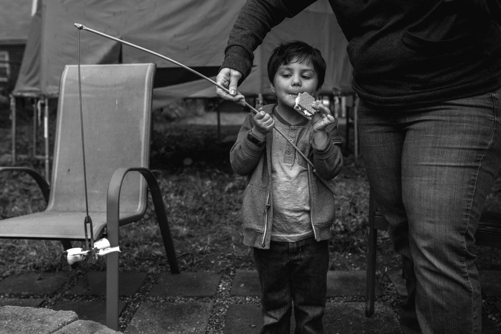 Boy eats a smore while holding a roasting stick with an adult