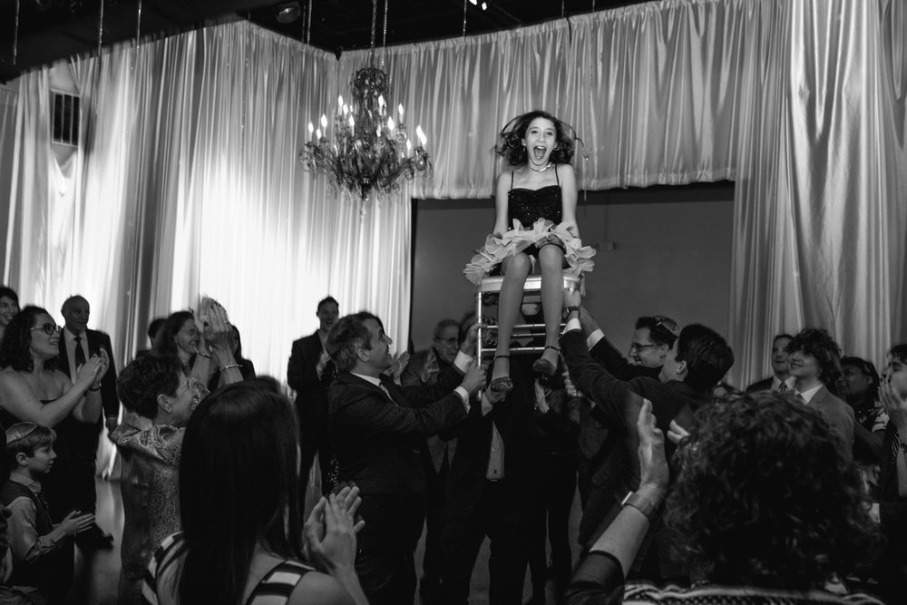 A girl sits on a chair in the air during a hora