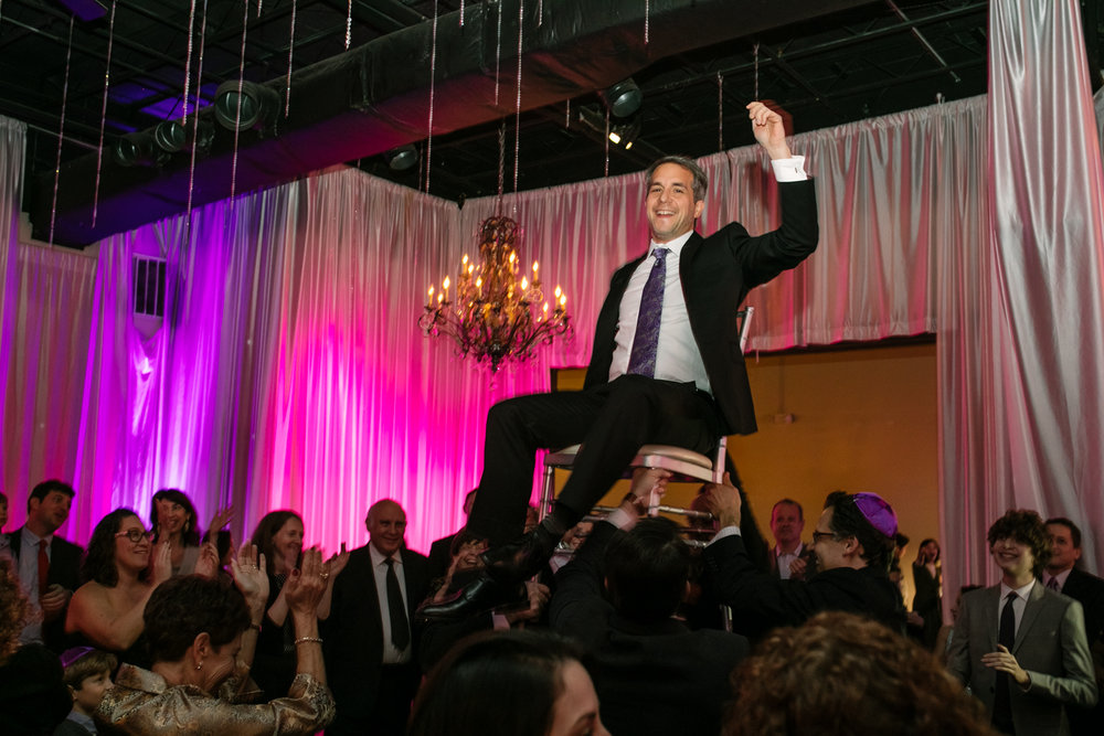 A man sits on a chair in the air during the hora