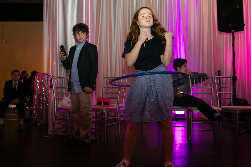 A girl hula hoops during a bat mitzvah as a boy looks on