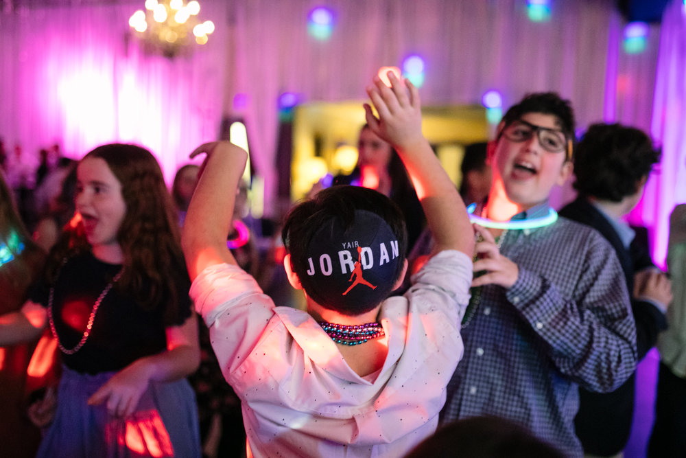 A boy with a yamaka dancing during a bat mitzvah