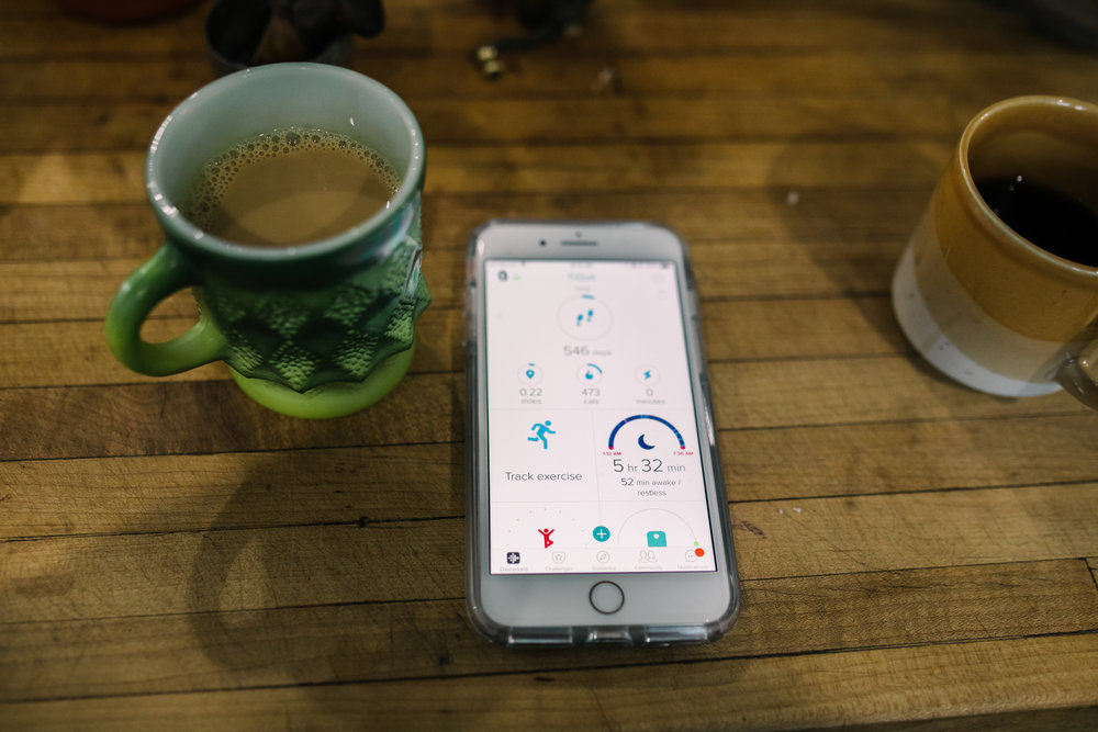 still life of coffee and phone with a sleep chart on a table