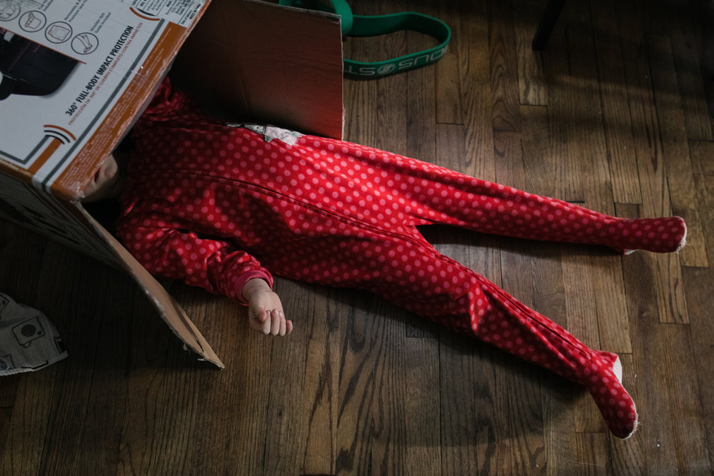 Child in red pajamas with head in the box while lying on the ground