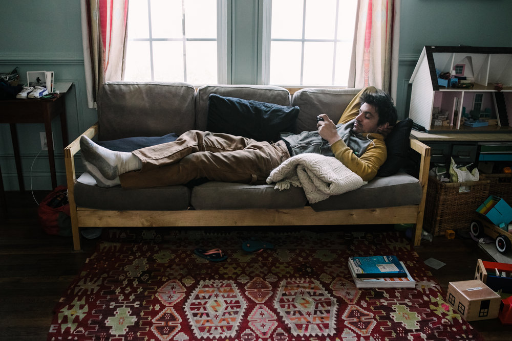 Man lies on a couch and looks at his phone
