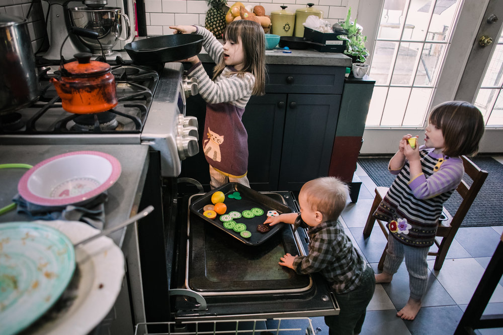 3 children play with pretend food in an oven