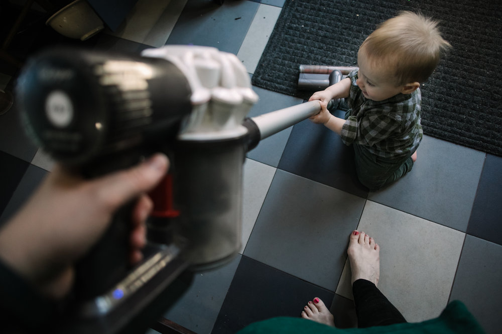 Mother vacuums while baby holds onto it taken from the mother's perspective
