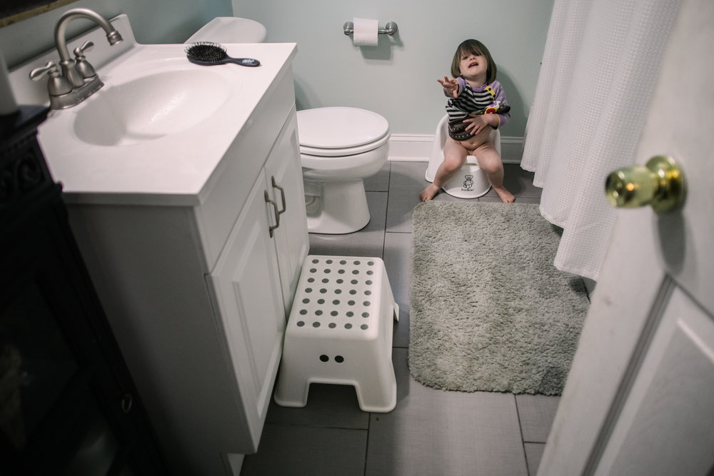 A toddler sits on a potty chair in a bathroom with her arm stretched out toward the person taking the picture