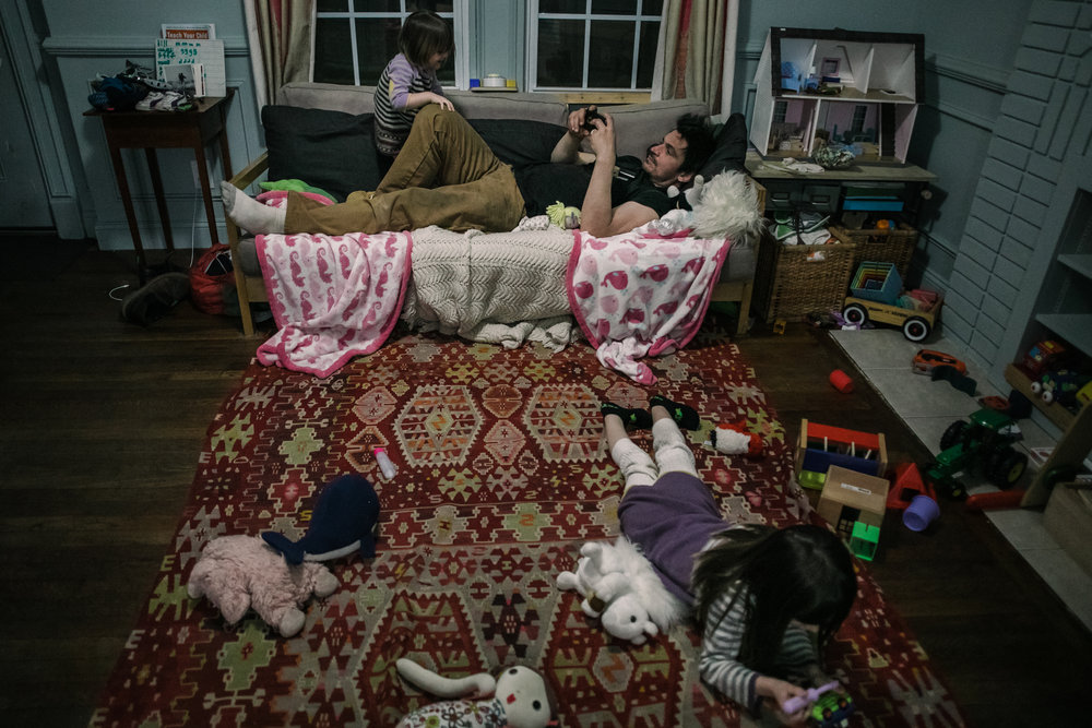 A man lies on a couch looking at his phone while a child climbs on him and another child lies on the floor in front of him