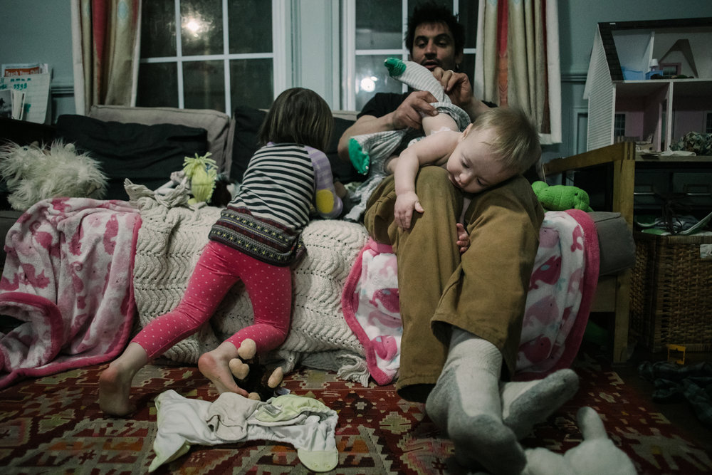 A father puts pajamas on a baby who is holding onto his leg and another child leans on a couch beside him