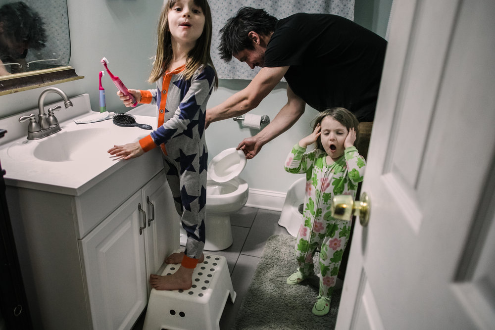 A girl yawns as a father dumps pee in a toilet and another girl looks at the camera while brushing her teeth