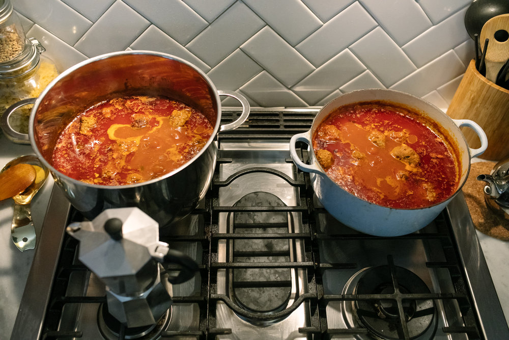two pots of meatballs cooking on a stove