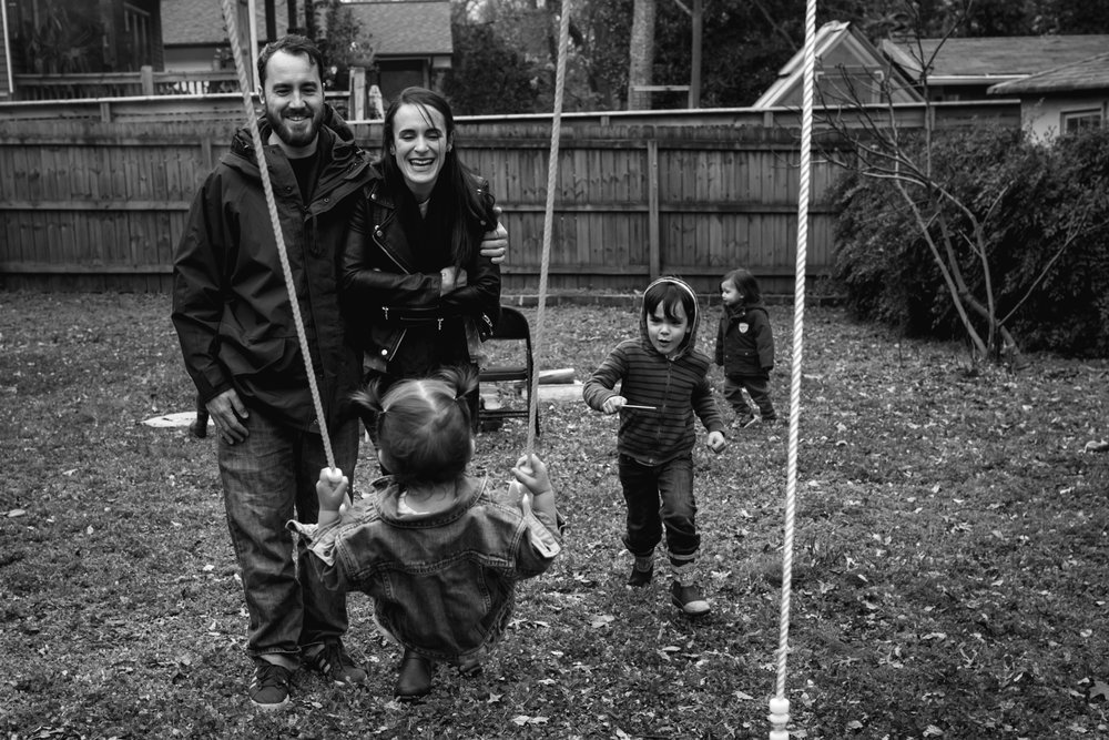 A mother and father look at their daughter as she swings in front of them