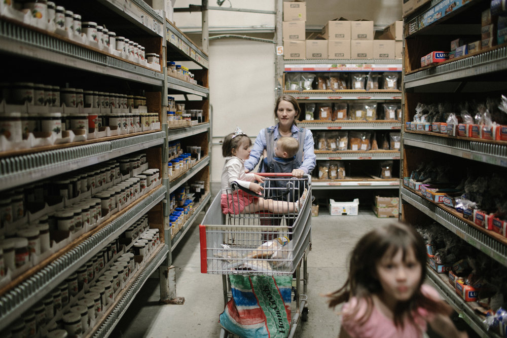 a mother pushes a cart down an aisle