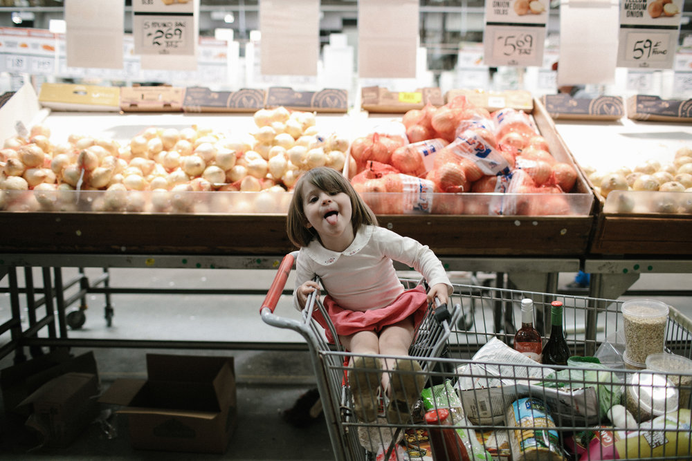a child in a cart sticks out her tongue at the person taking the photo in the onion aisle