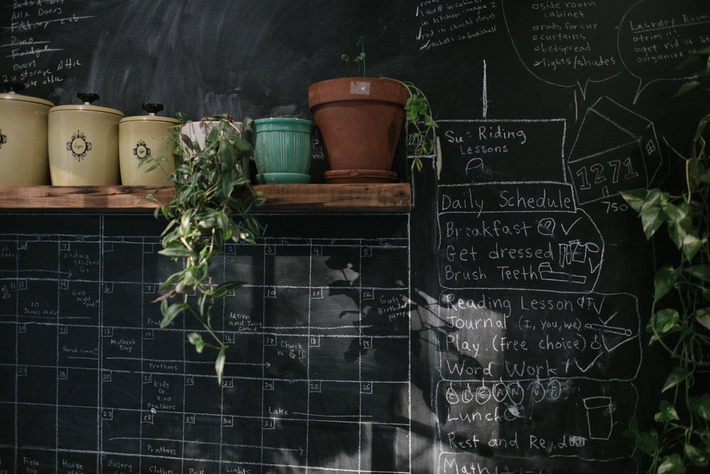 a chalkboard wall and a shelf with plants and cookbooks