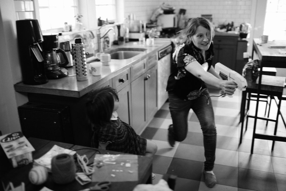 a woman runs through the kitchen playing laser tag