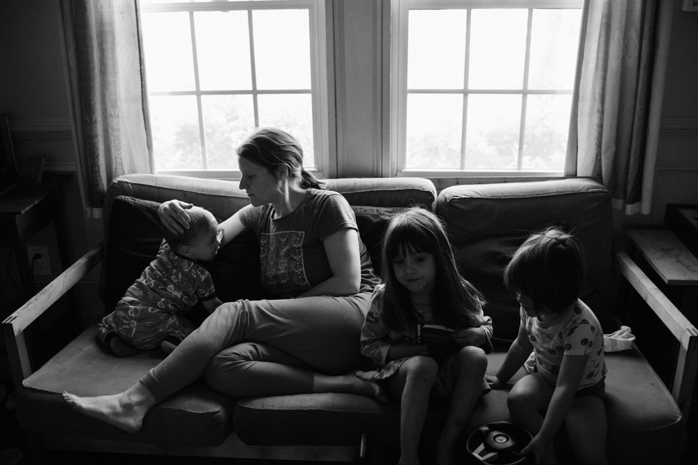 A mother sits on a couch with her three children