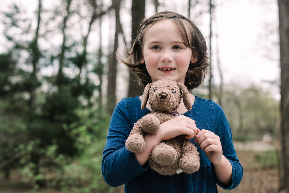 a girl smiles and holds a stuffed animal dog