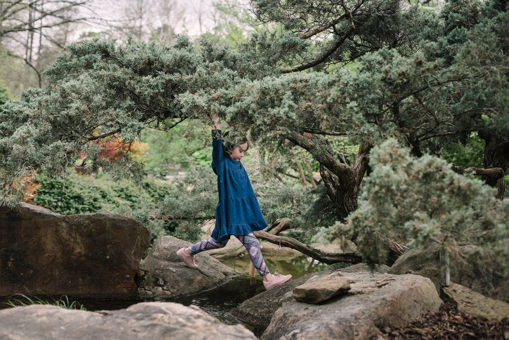 a girl climbs over rocks under a tree