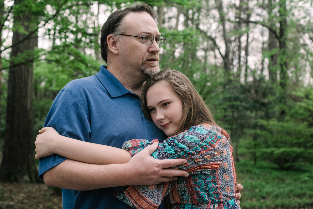 a girl hugs her dad who rests his chin on her head