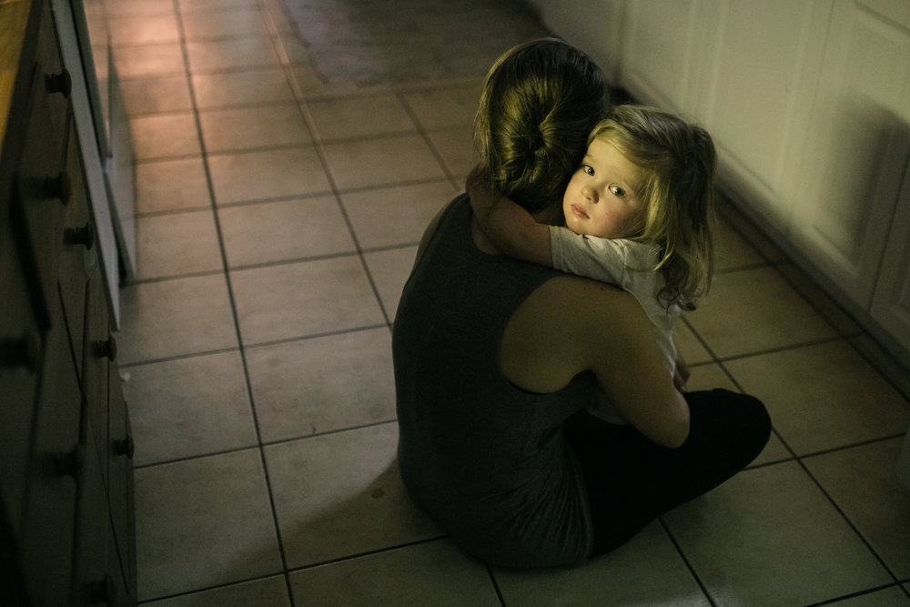 girl with arms around her mother's neck on a tiled floor