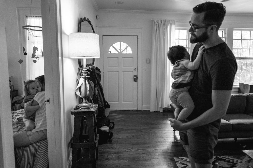 A man holds a baby and looks into a room with a mom and a daughter