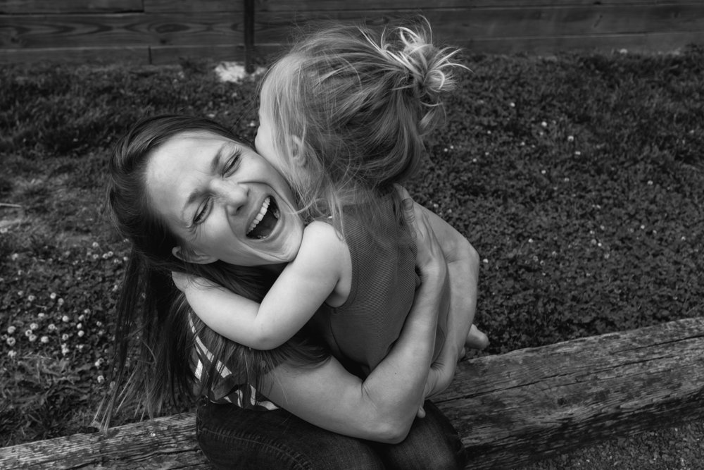 a mother smiles while embracing her daughter